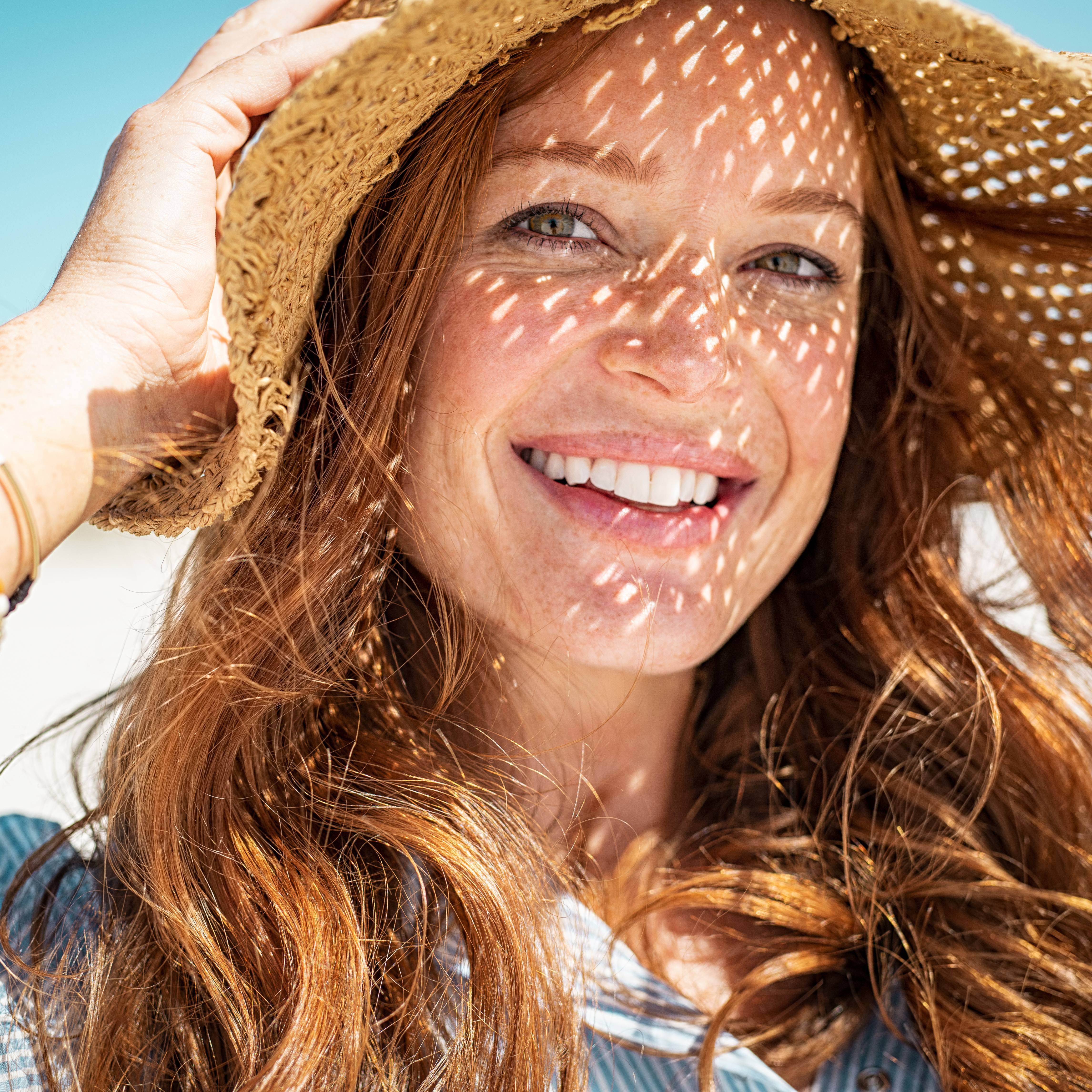 a smiling middle-aged woman in a straw hat outside on a sunny day
