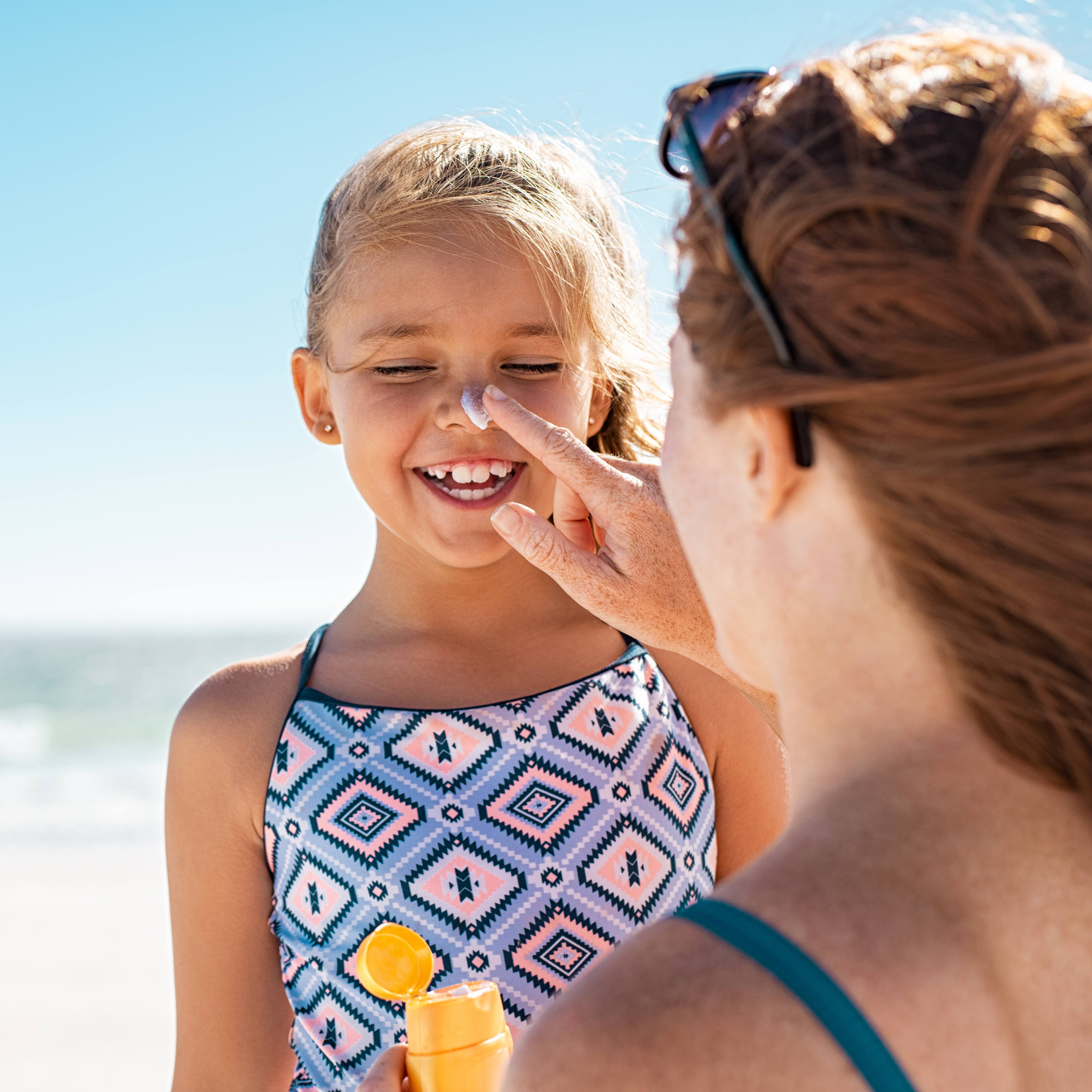 a woman applying sunscreen to the nose of a laughing young girl at the beach
