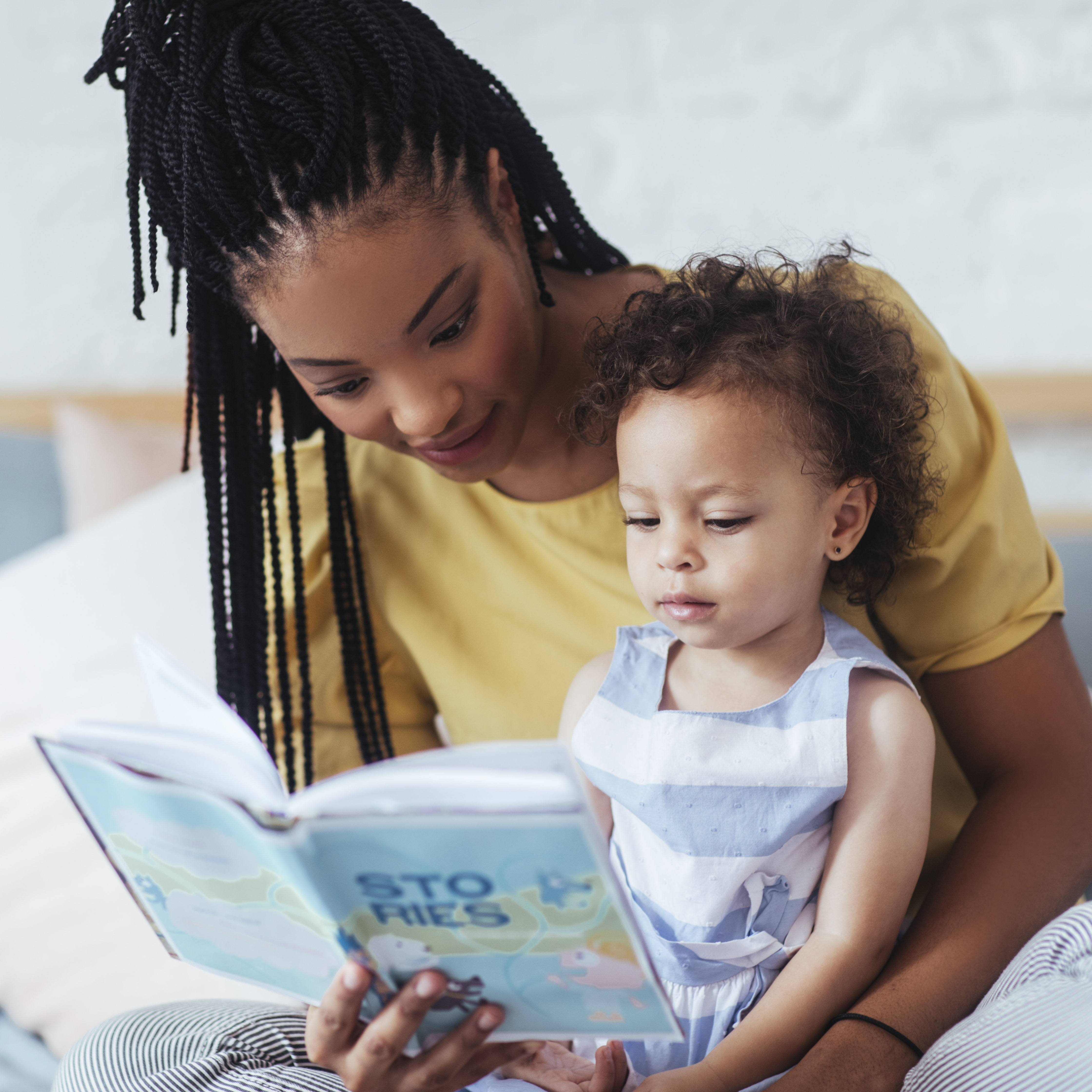 a young mother and her toddler daughter sitting together on a bed, reading a book