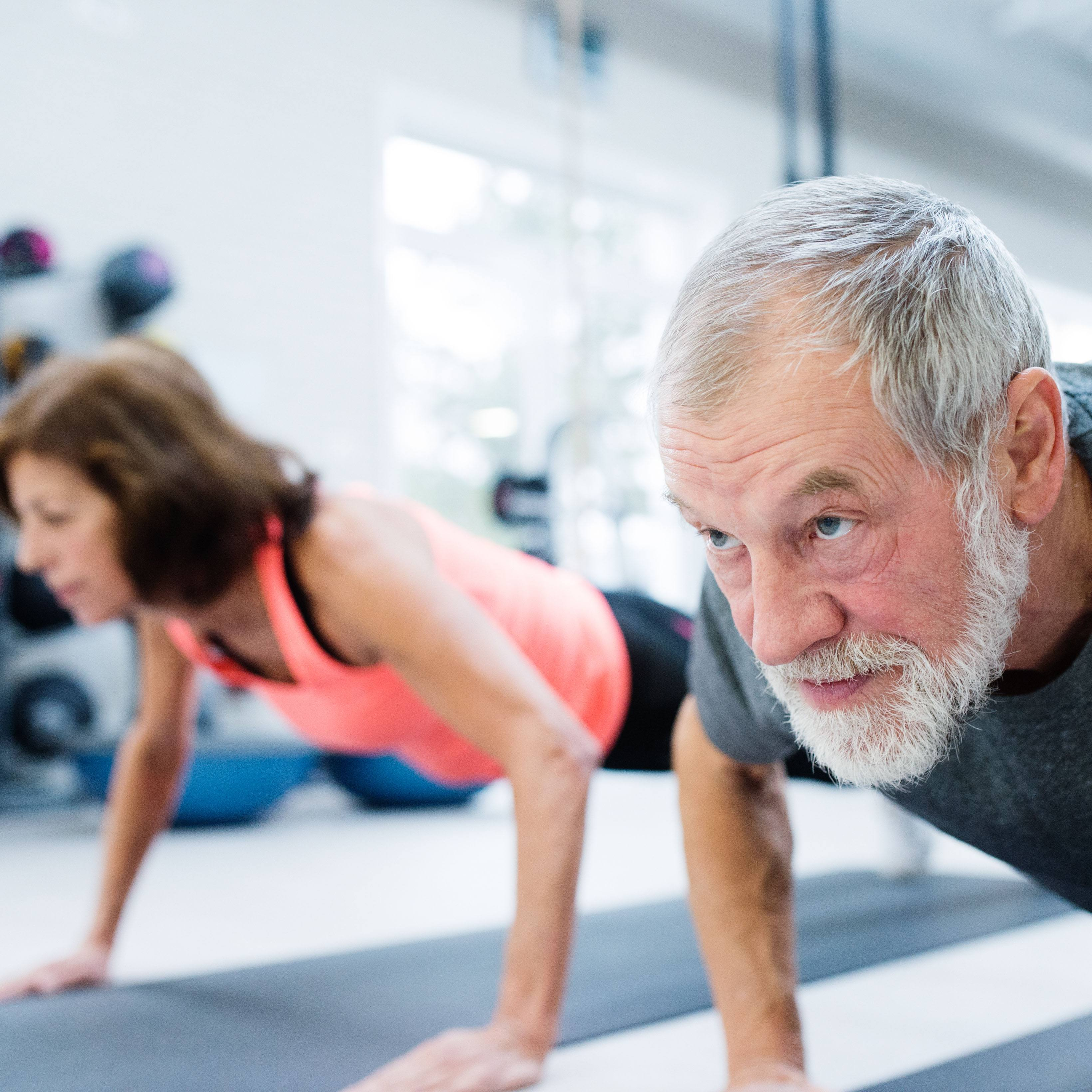 an older couple working out together in a gym, doing push-ups