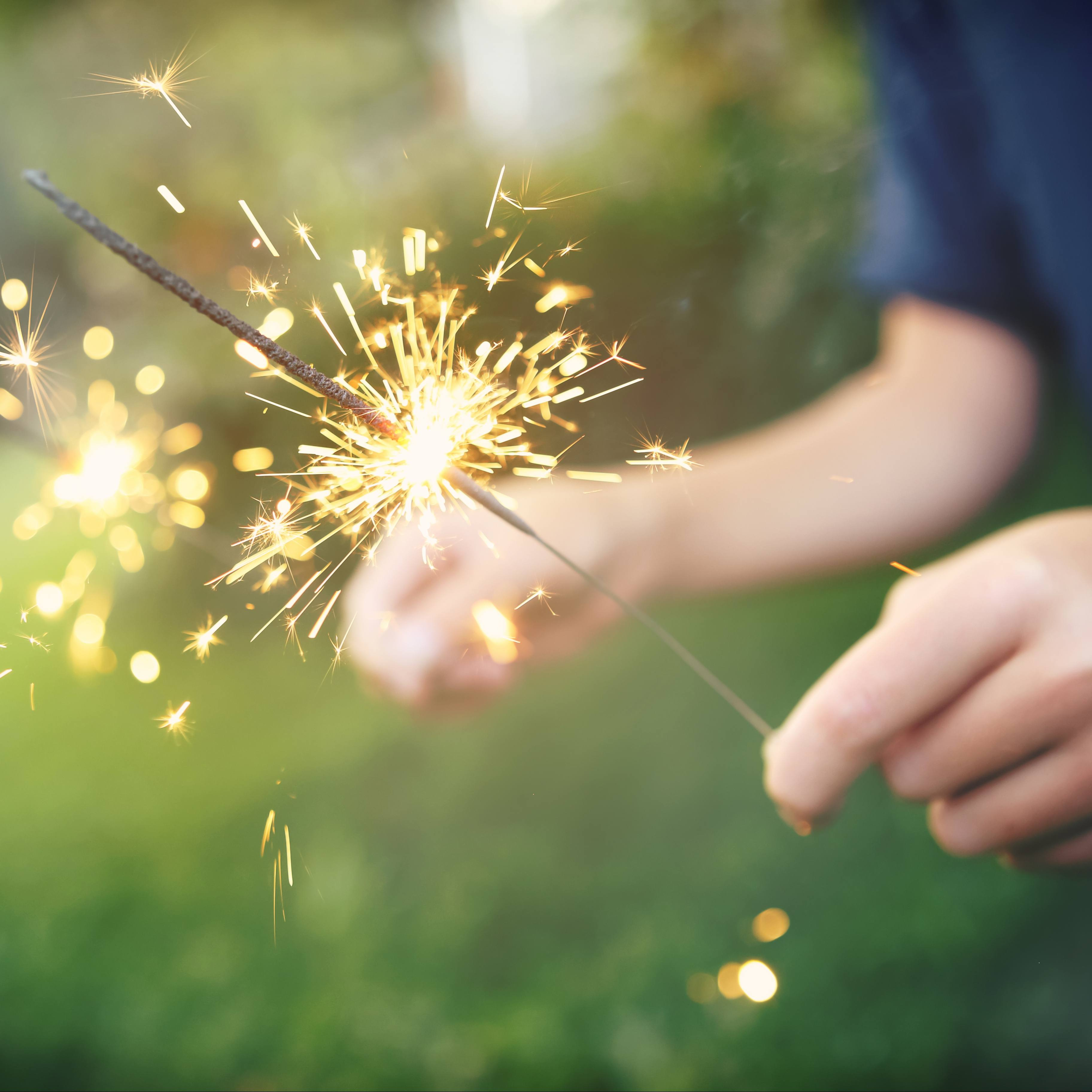 a young person lighting a fireworks sparkler in their hands