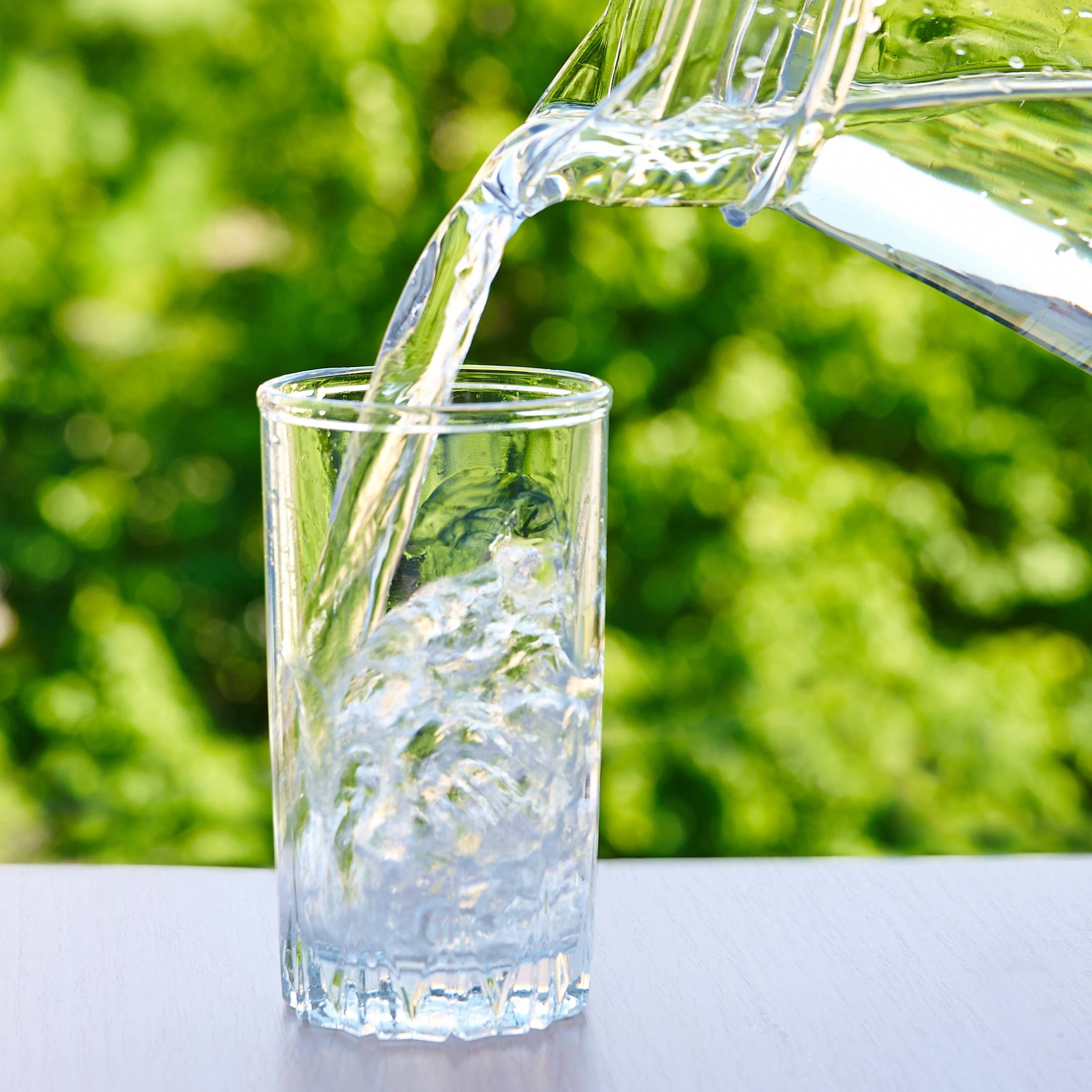 a glass pitcher of water with someone pouring it into a glass with ice cubes