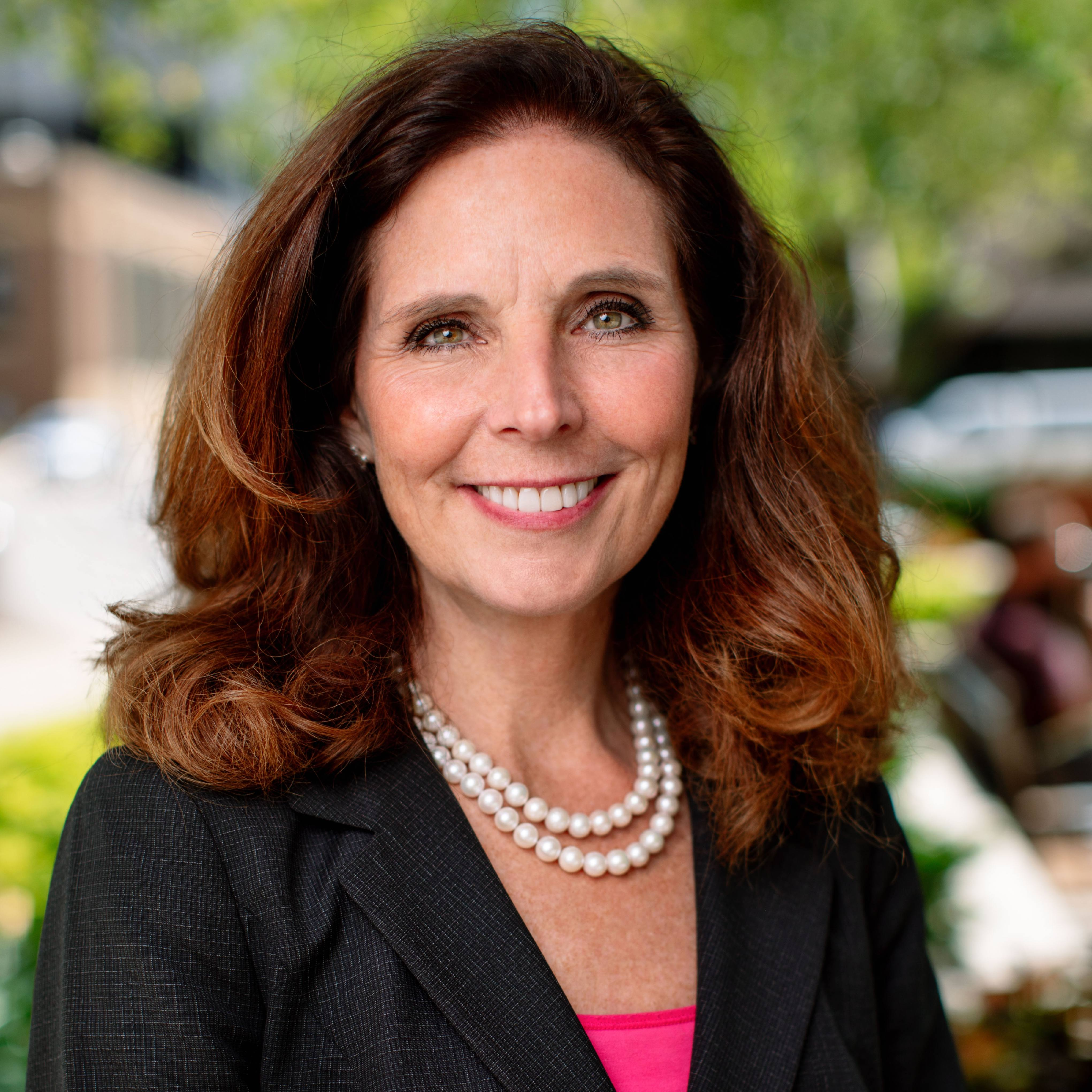 Dr. Amy Williams outside, wearing a professional suit with pearls, smiling