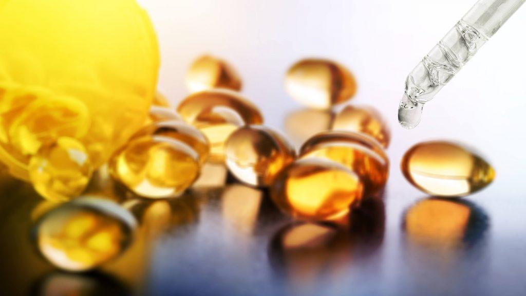 Cápsulas de aceite de cannabidiol (CBD) regadas de un frasco y un gotero con CBD con un trasfondo blanco.