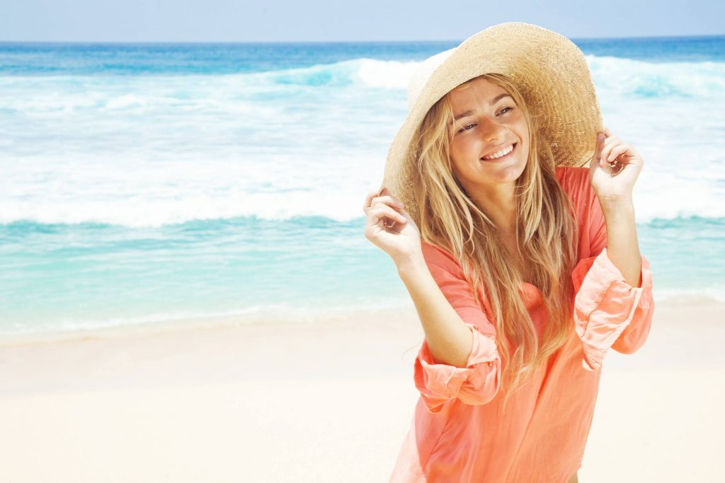a smiling young woman at the beach, wearing a large straw hat