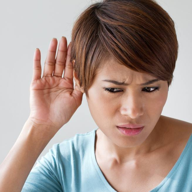 a young woman holding her hand to her ear trying to hear or listen to someone talking or a noise