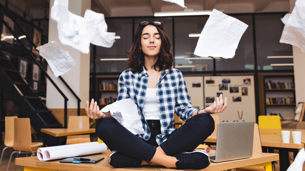 a young woman deep in thought, meditating on an office desk with work papers floating in the air