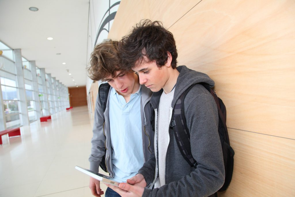 teenage boys looking at a hand-held mobile device, an electronic tablet while standing in a school hallway