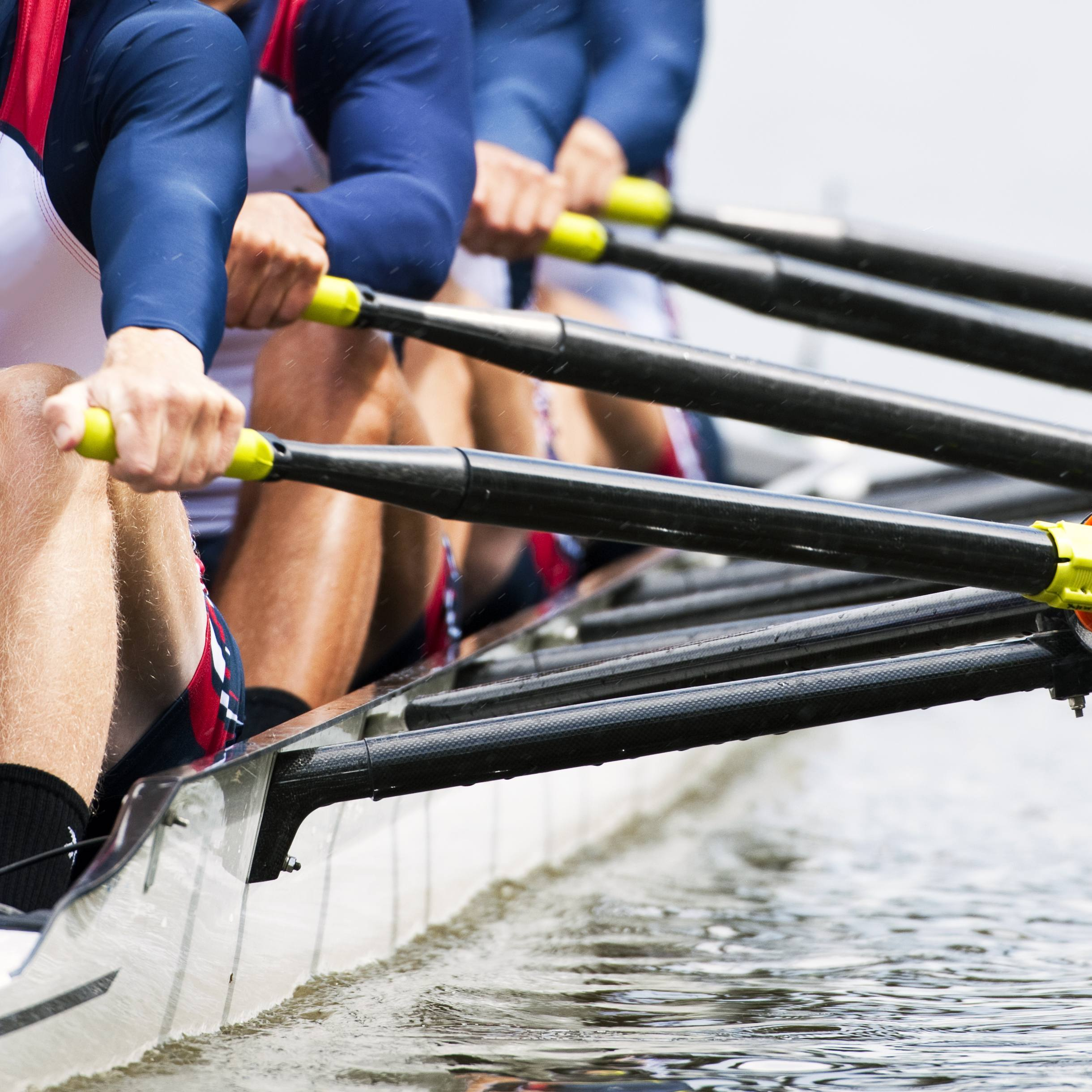 a sports rowing team in their shell or boat, paddling on the water, exercising and racing as a team