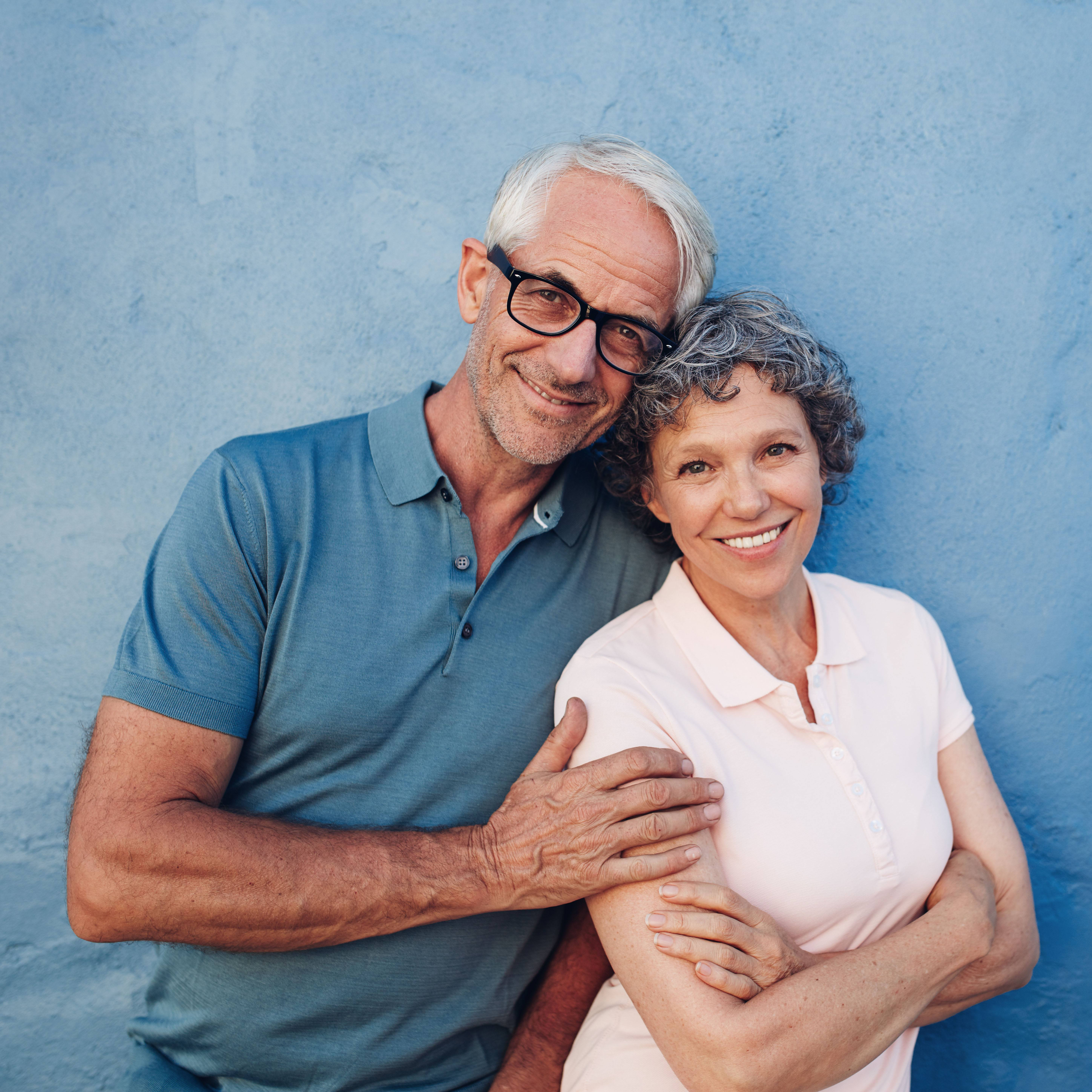 a happy, smiling middle-aged couple standing together in front of a blue wall