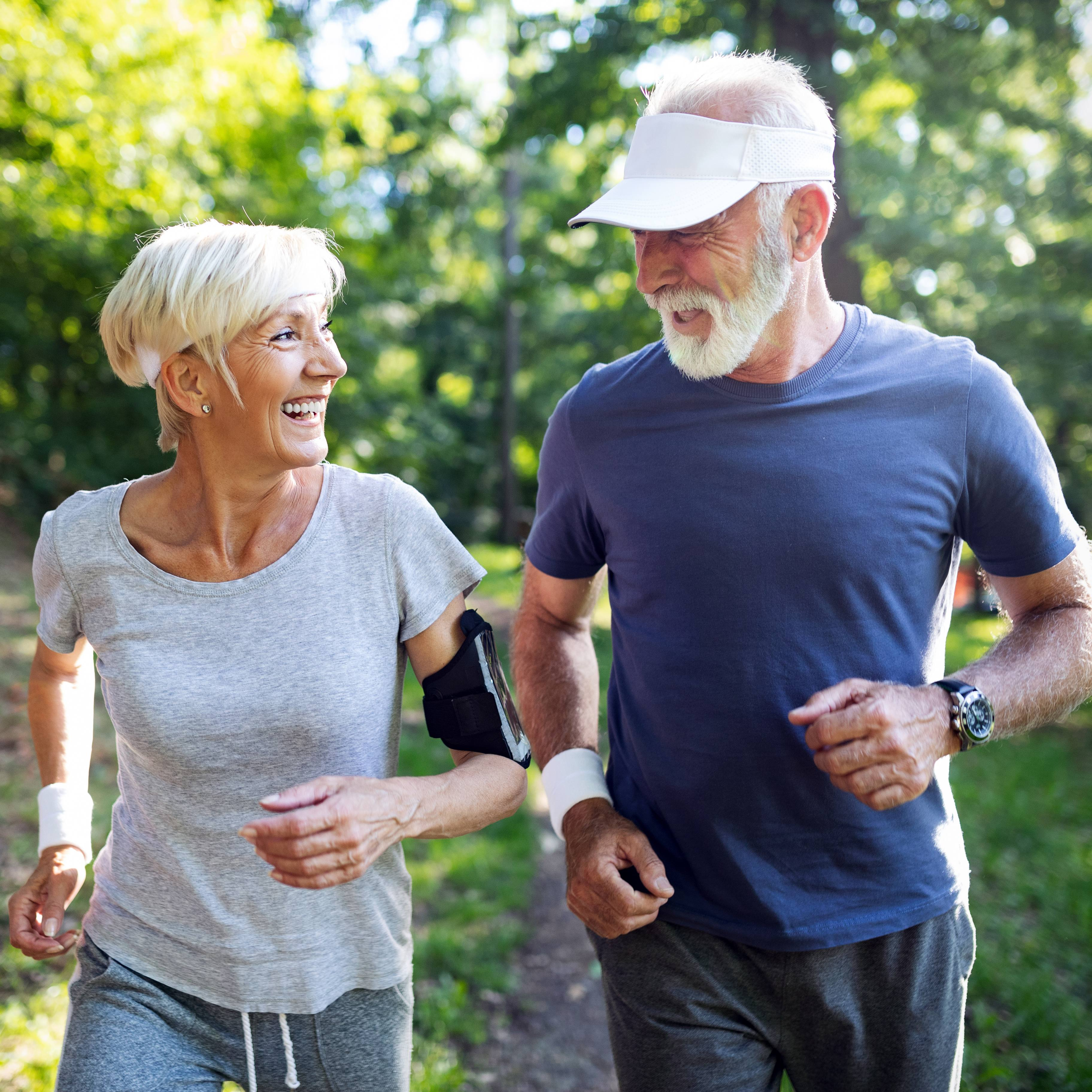a happy, smiling older couple running on a path in a sunny park