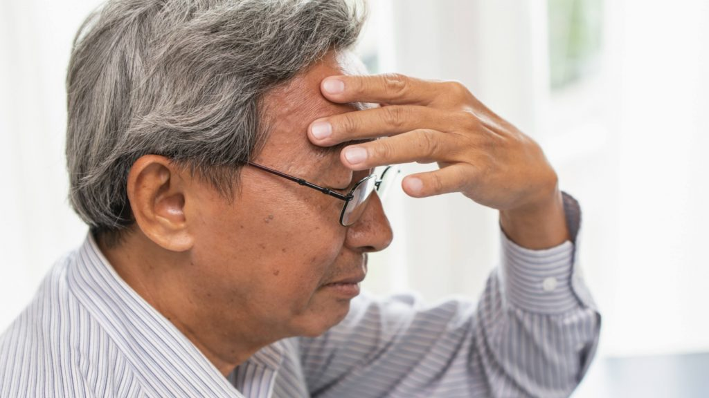 a middle-aged man wearing glasses and holding his hand to his head,looking sad and worried, maybe depressed and trying to remember something