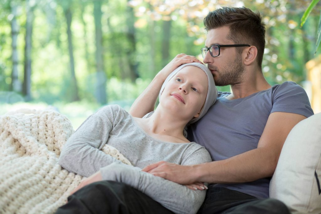 a young couple sitting on a couch or bed with a blanket, comforting each other, perhaps after the woman has had chemotherapy treatment for cancer.