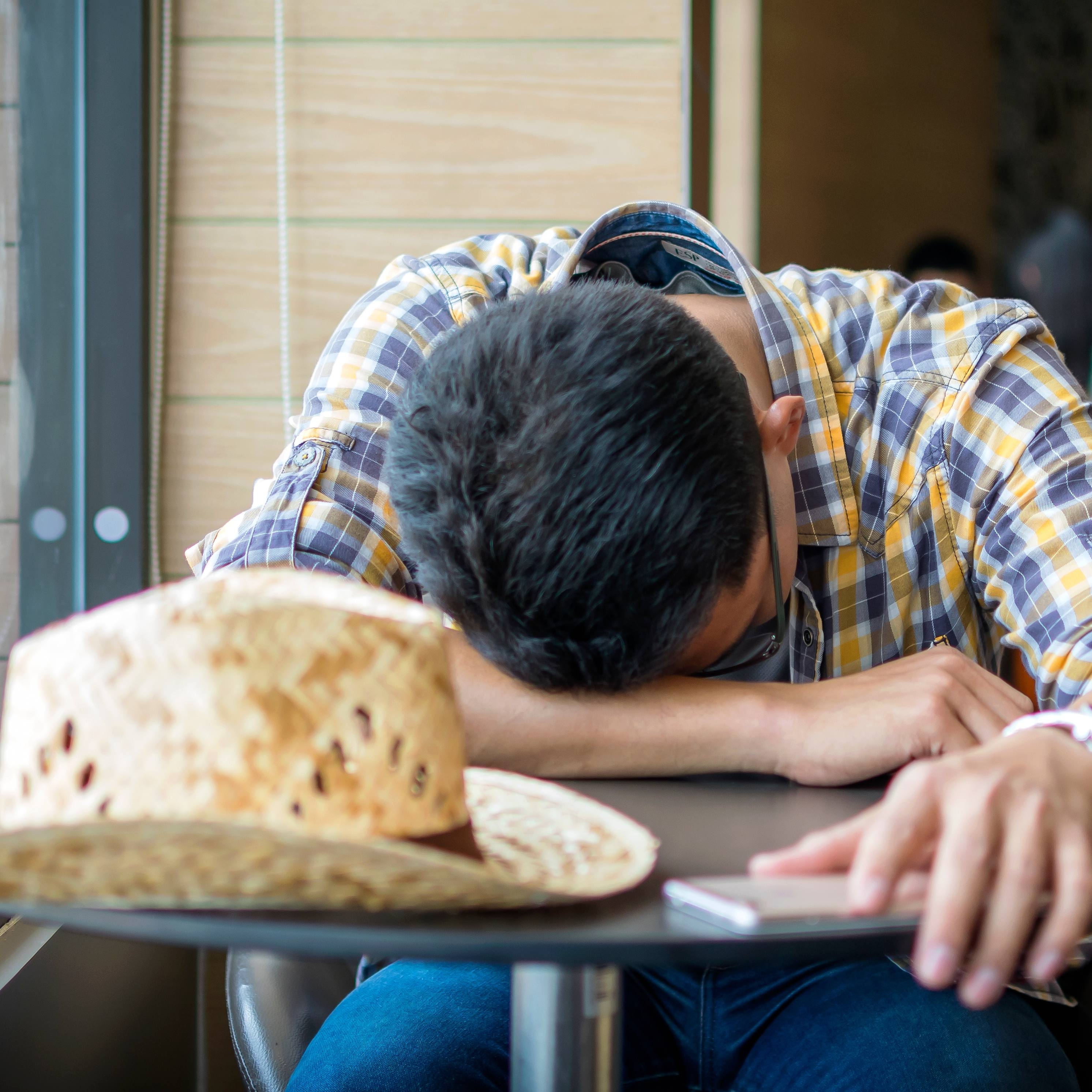 a young man, perhaps a farmer, looking sad, tired, depressed with his hat on a table and his head down on his arm.
