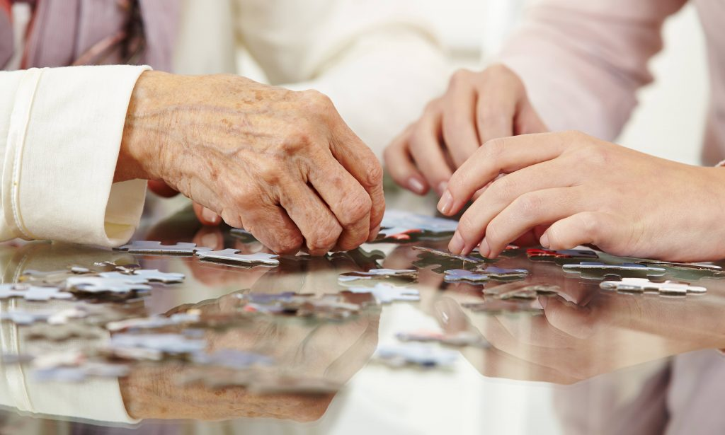 an eldery person's hands and a young adult person's hands working with puzzle pieces on a table, working on memory and cognitive health