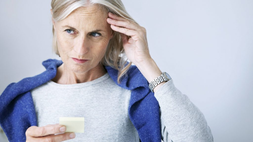 a middle-aged woman looking concerned and holding a small piece of paper, perhaps a list or reminder note, with her hand to her head trying to remember something