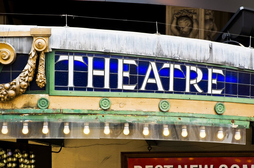 a section of an old, ornate theatre entrance, with the word THEATRE in stained glass
