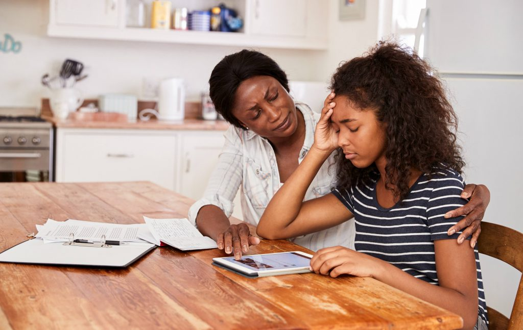 a mother comforting a stressed teenage daughter at the table in their kitchen