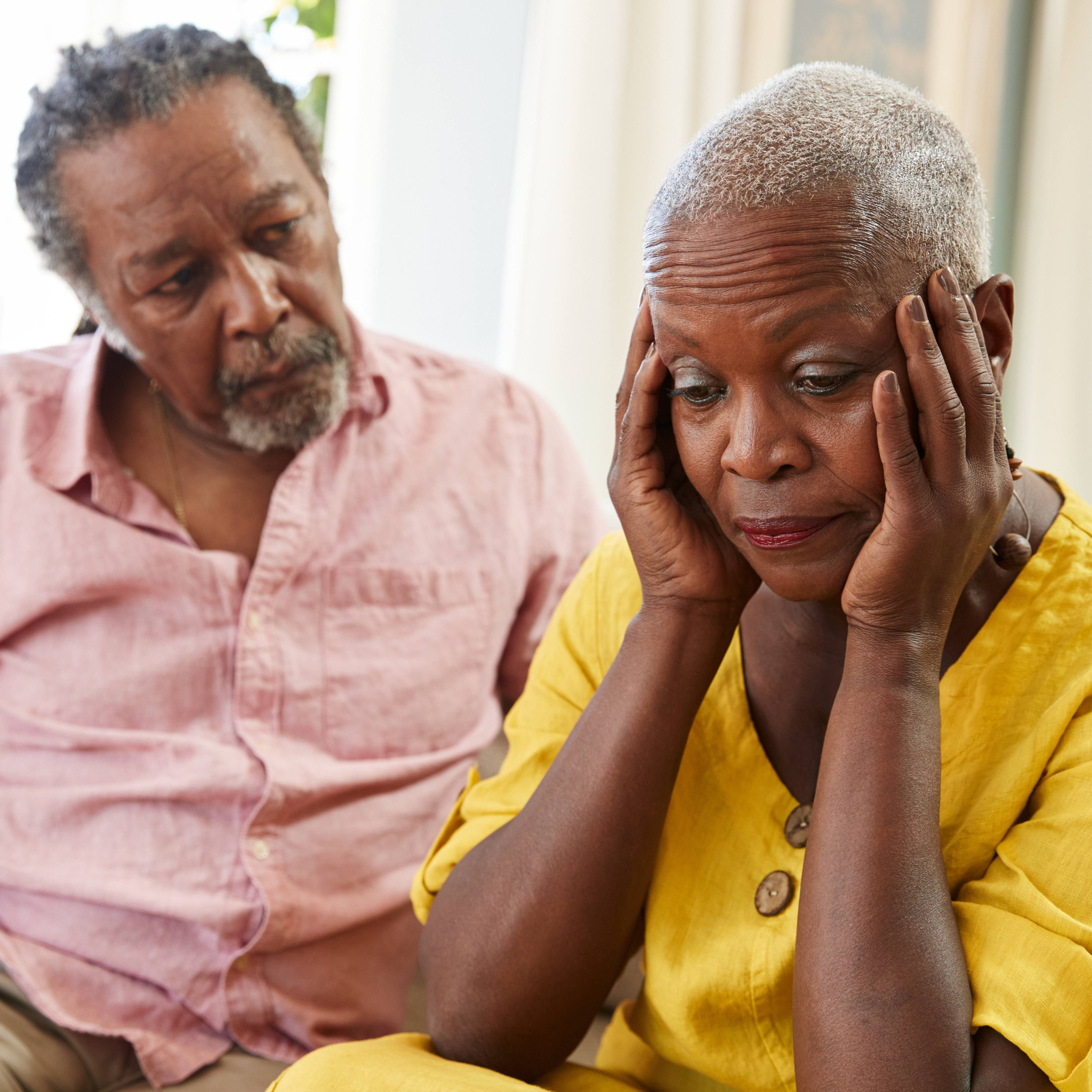 an older couple, a man and a woman, sitting on a couch together looking worried, concerned, sad as the woman holds her head in her hands perhaps having some depression or memory and cognitive function problems