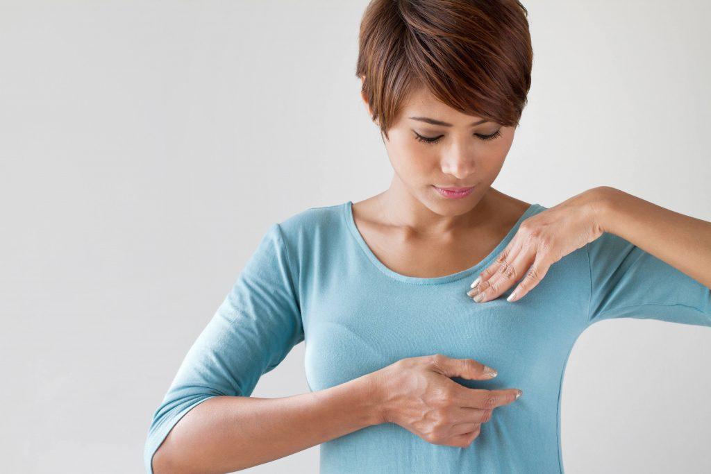 Mujer con camisa azul haciendo autoexamen de mamas