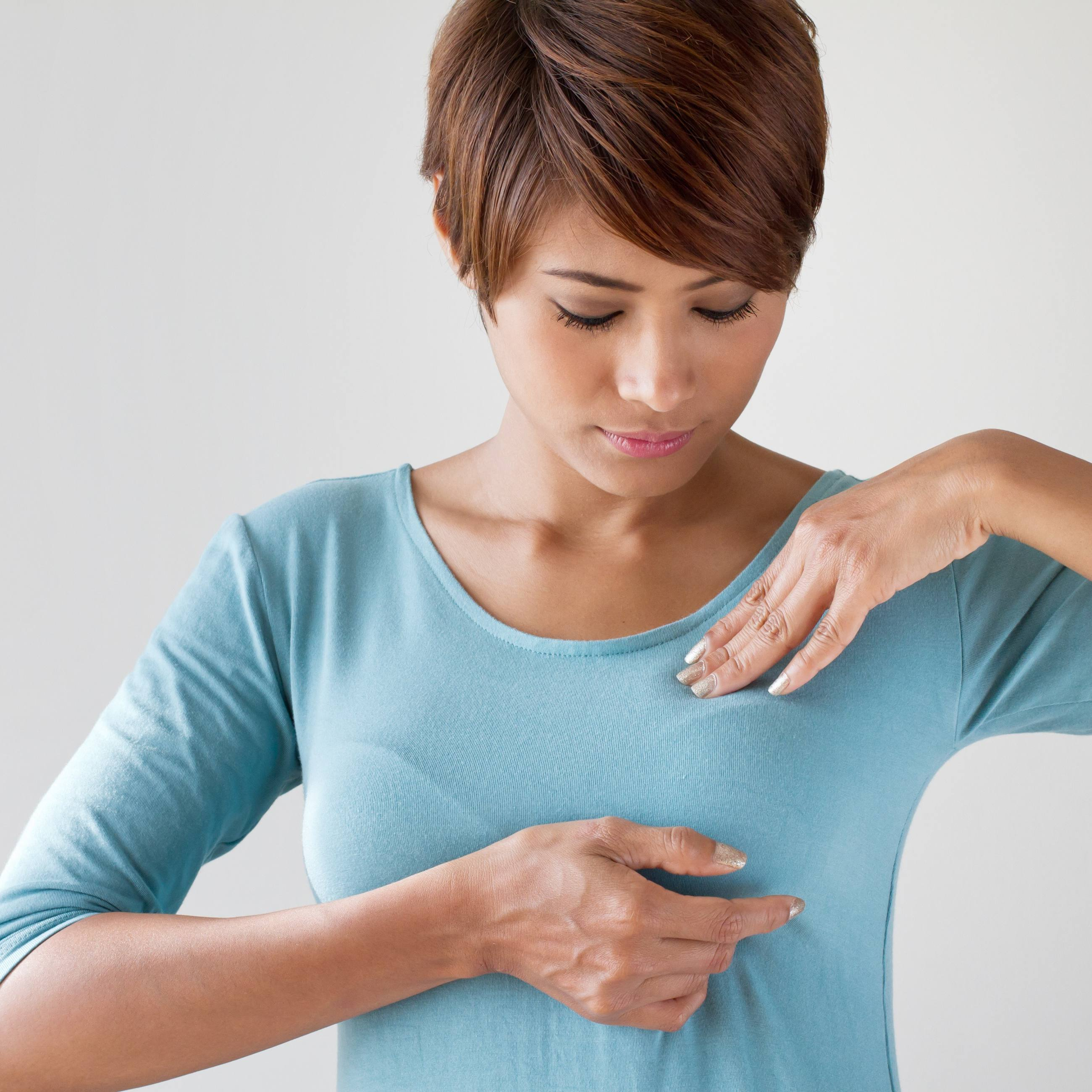 Woman wearing blue shirt doing breast self-examination