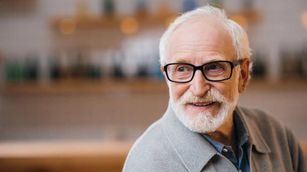 Un acercamiento de un hombre mayor con cabello y barba blanca que usa lentes