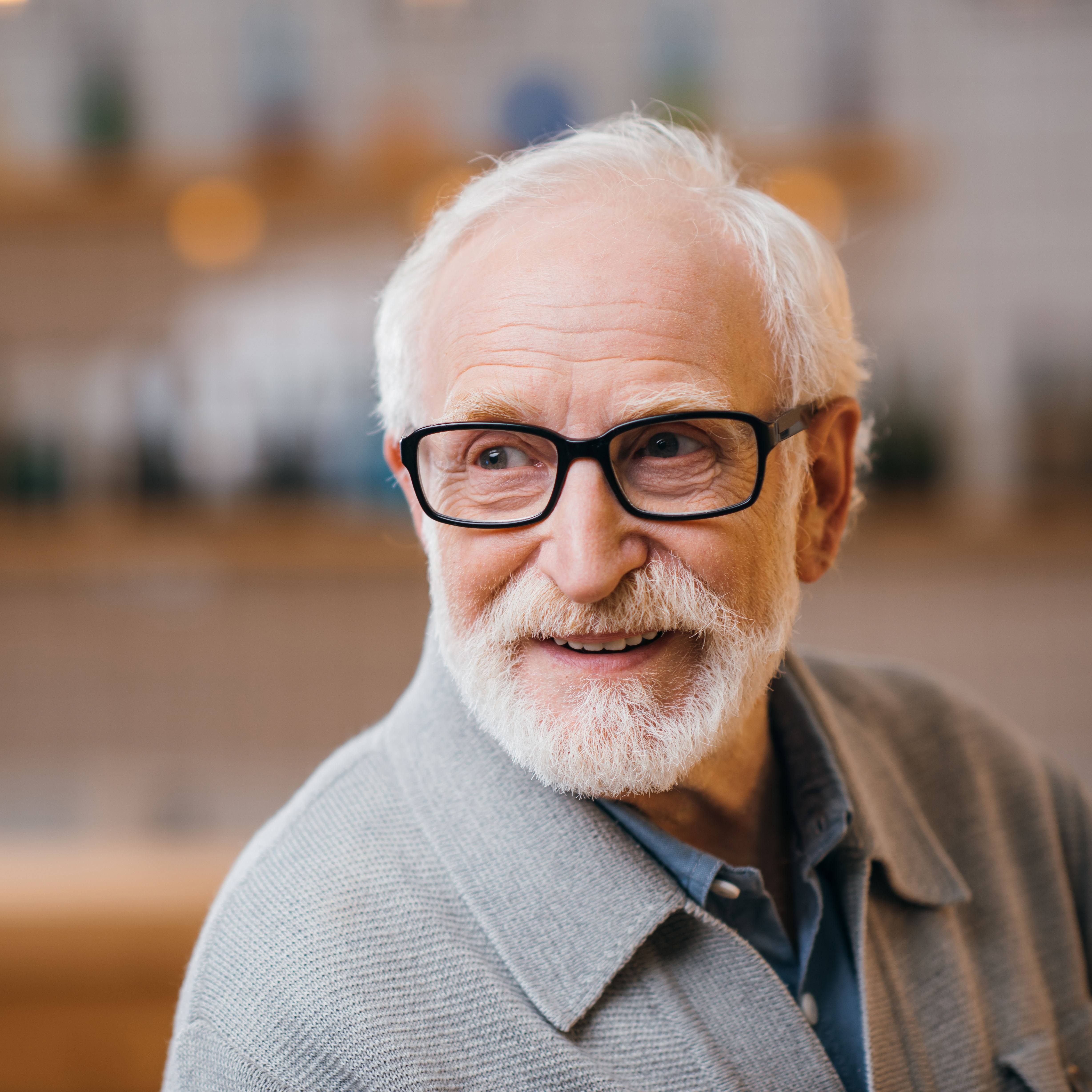 a close-up of a smiling elderly man, with white hair and a white beard, wearing glasses