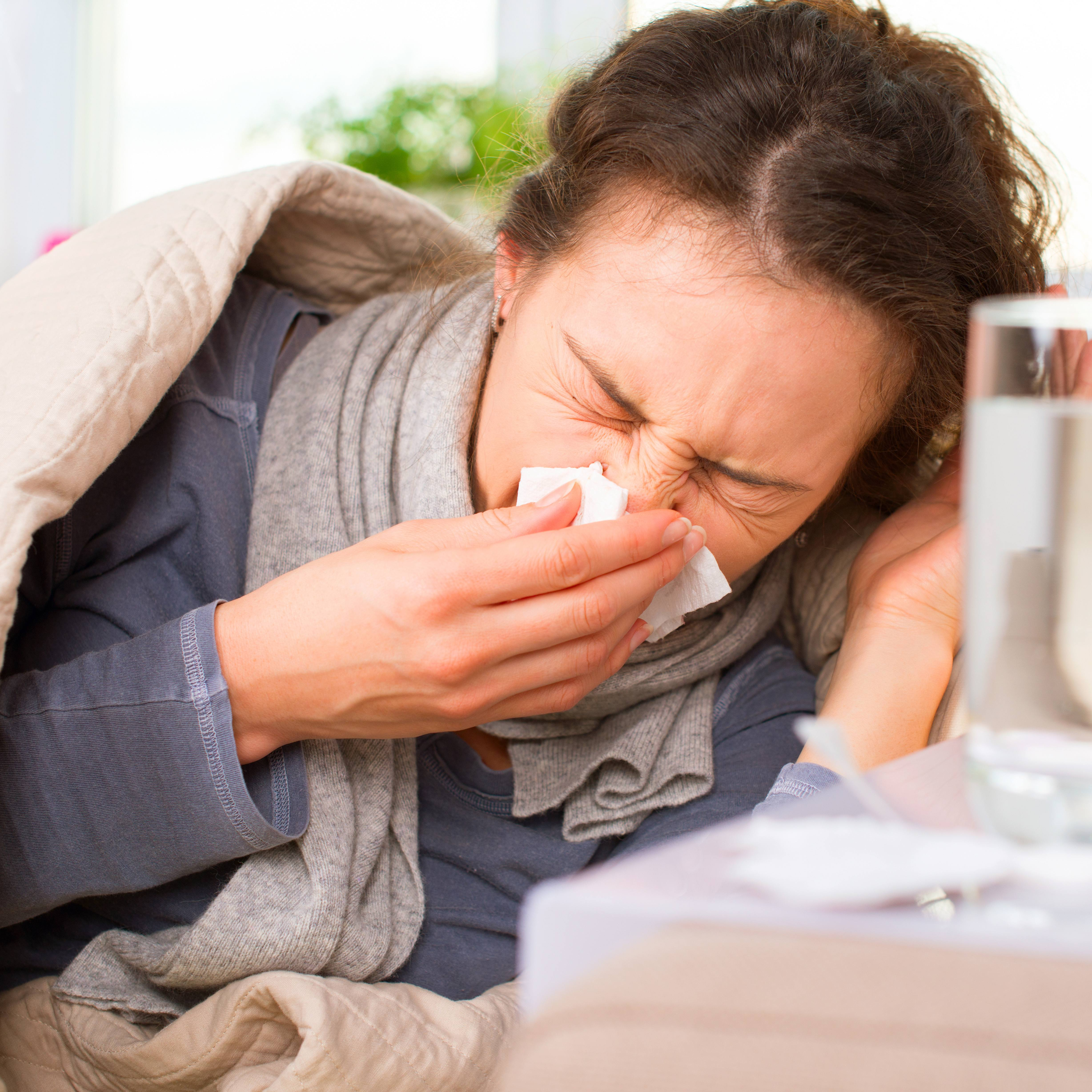 a middle aged woman sick in bed, sneezing into a tissue