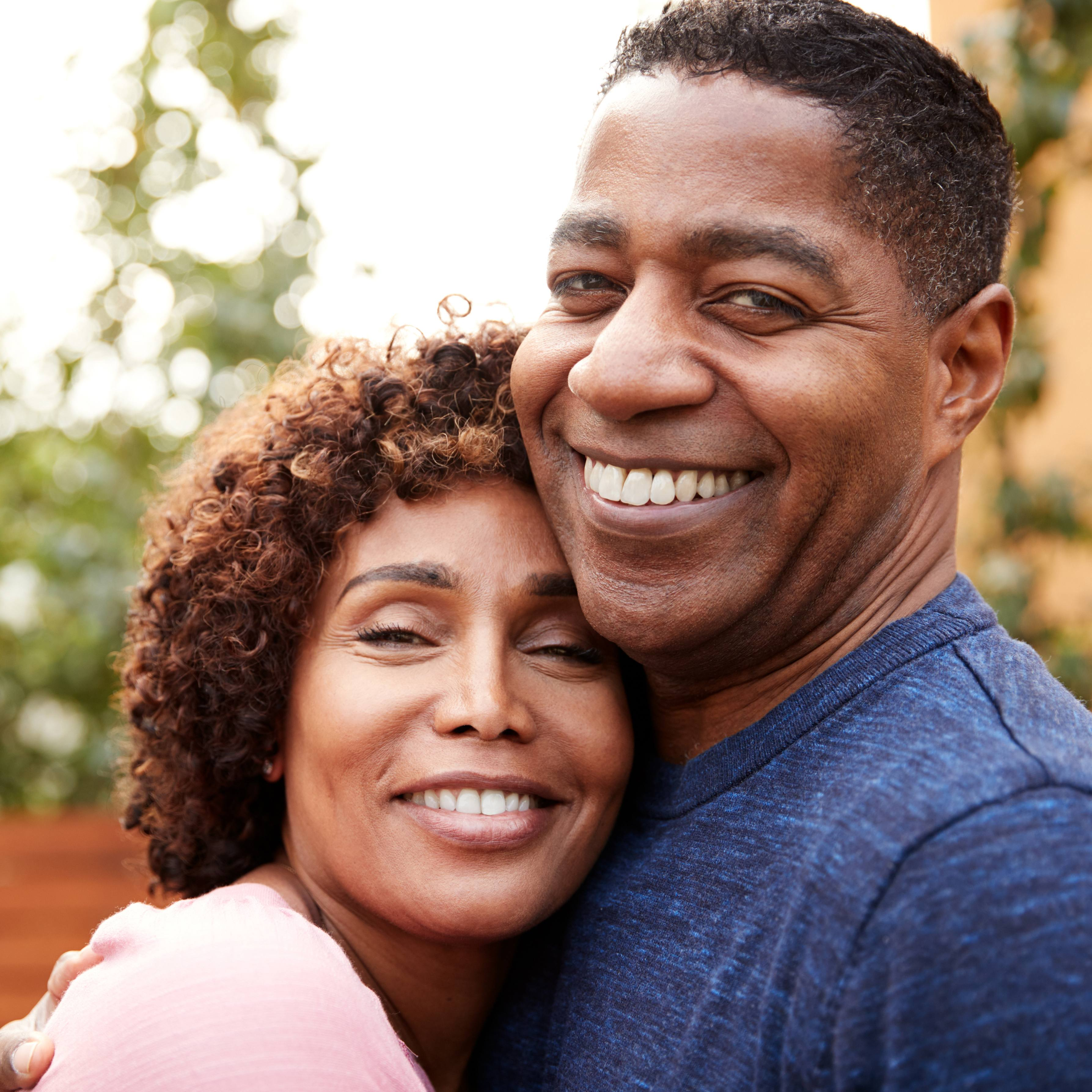 a smiling middle-aged couple outdoors on a sunny day, embracing