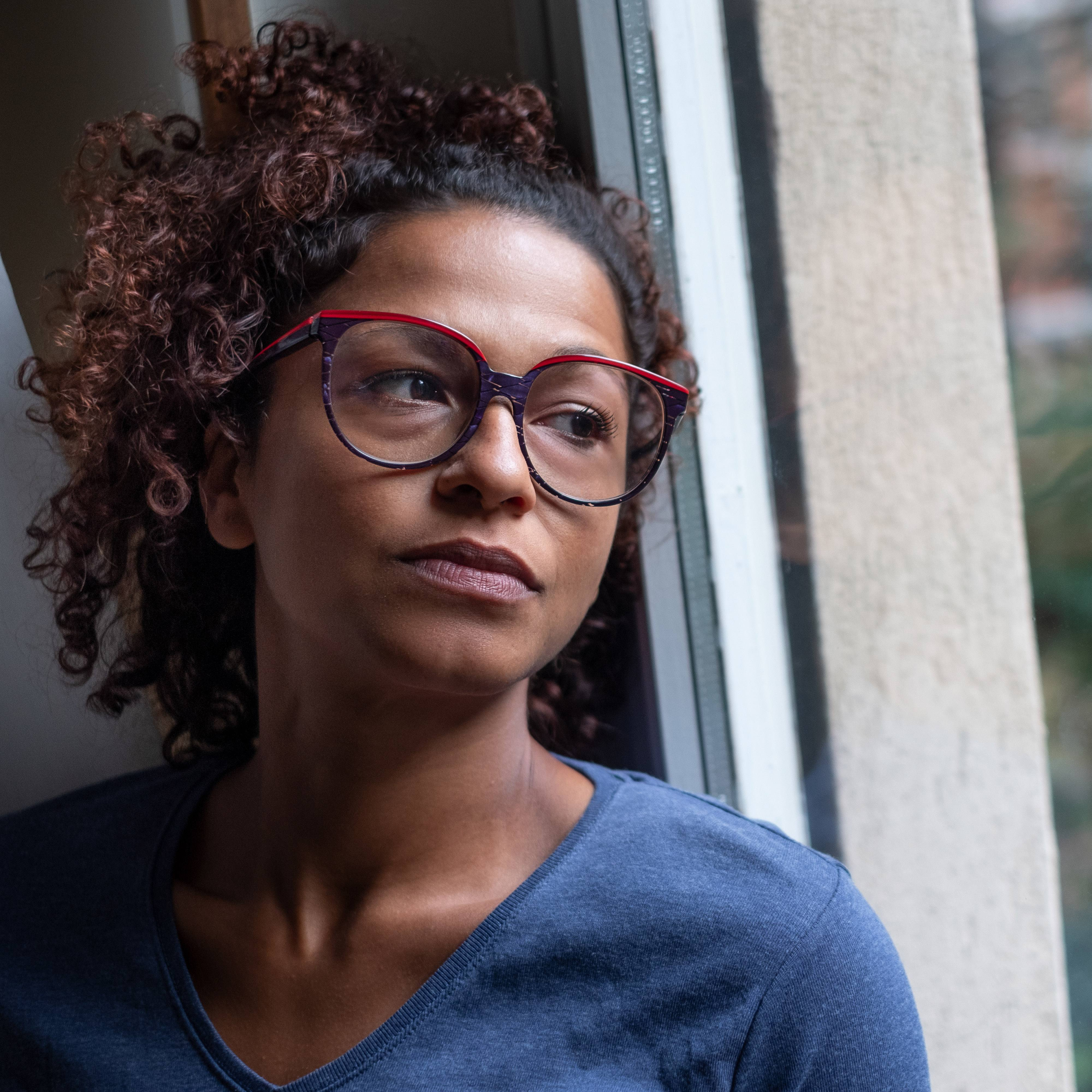 portrait of a middle-aged woman standing near a window, looking sad, depressed, lonely