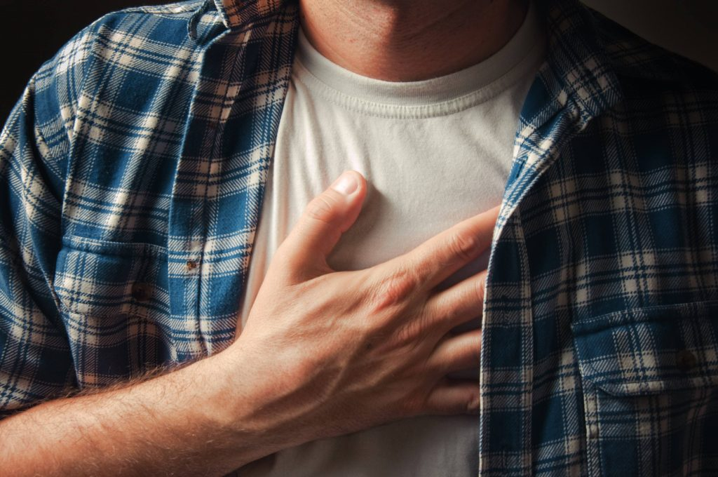 a Caucasian man with his hand on his chest as if he's suffering with pain, heart attack, heartburn, acid reflux, GERD