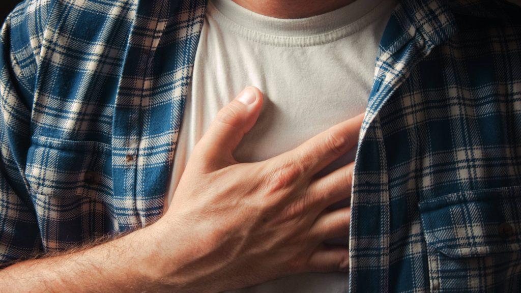 hombre con la mano en el pecho como si estuviera sufriendo de dolor, ataque cardíaco, acidez de estómago, reflujo ácido, ERGE
