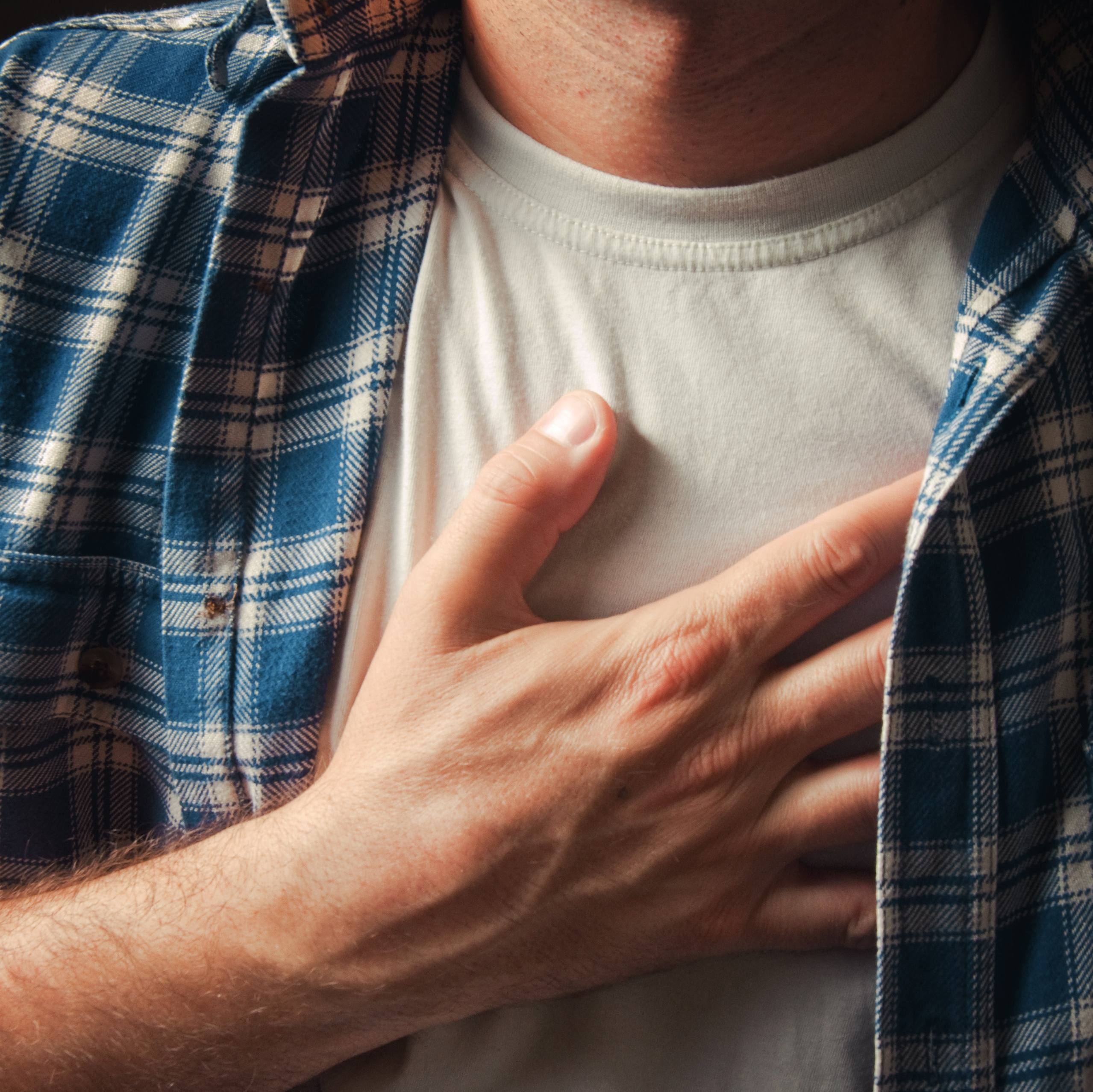 a Caucasian man with his hand on his chest as if he's suffering with pain, heart attack, heartburn