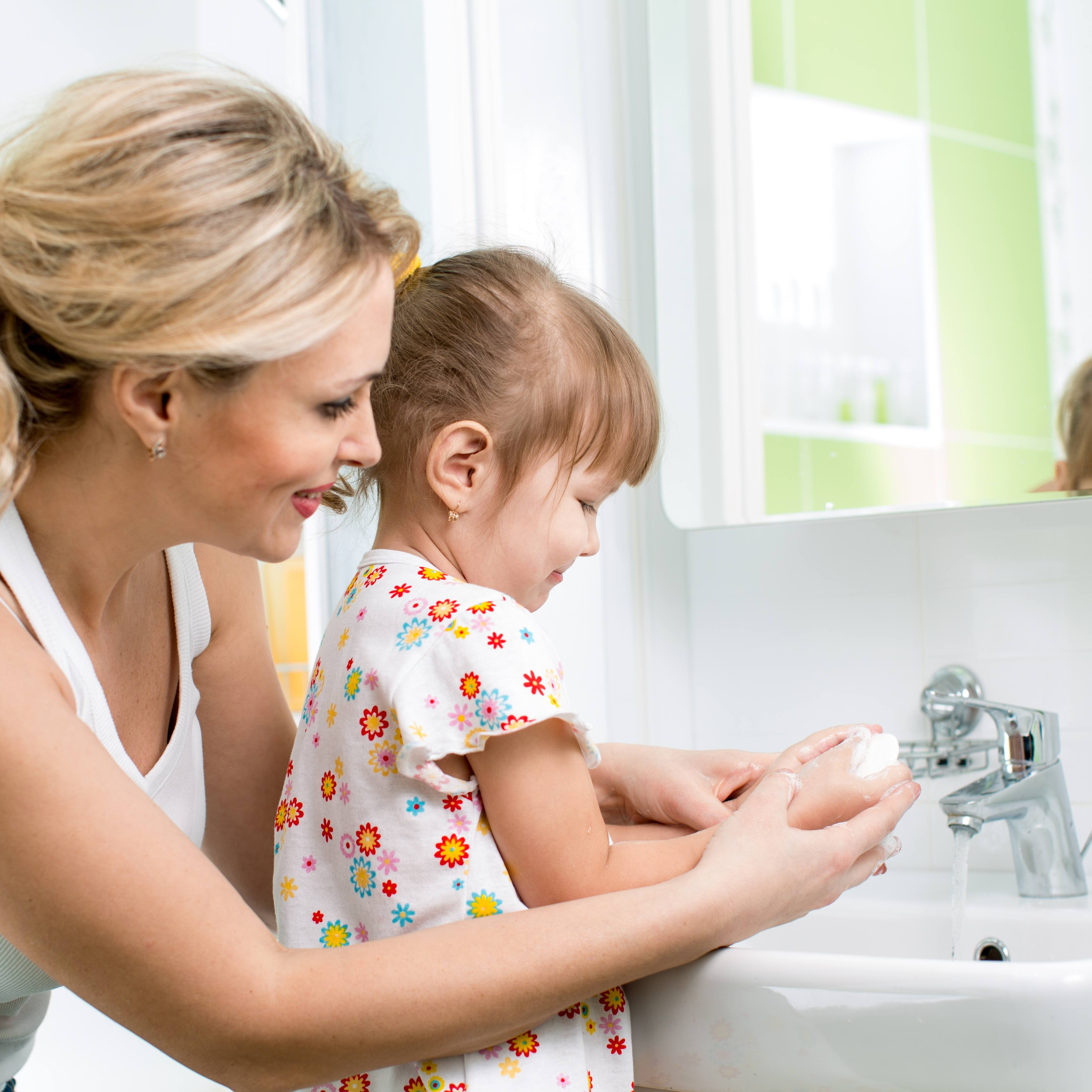a young women with a child at a bathroom sink helping the little girl wash her hands