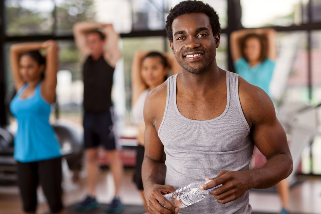 a smiling young man in an exercise class at a gym