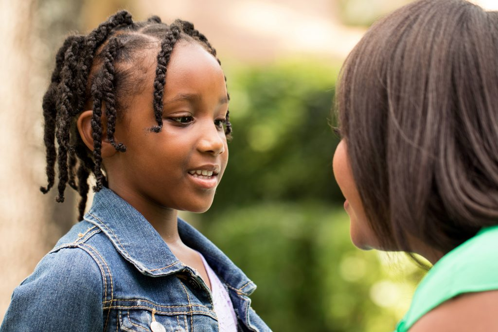 a young African American girl in a denim jacket, smiling and listening to an African American woman, perhaps her mother