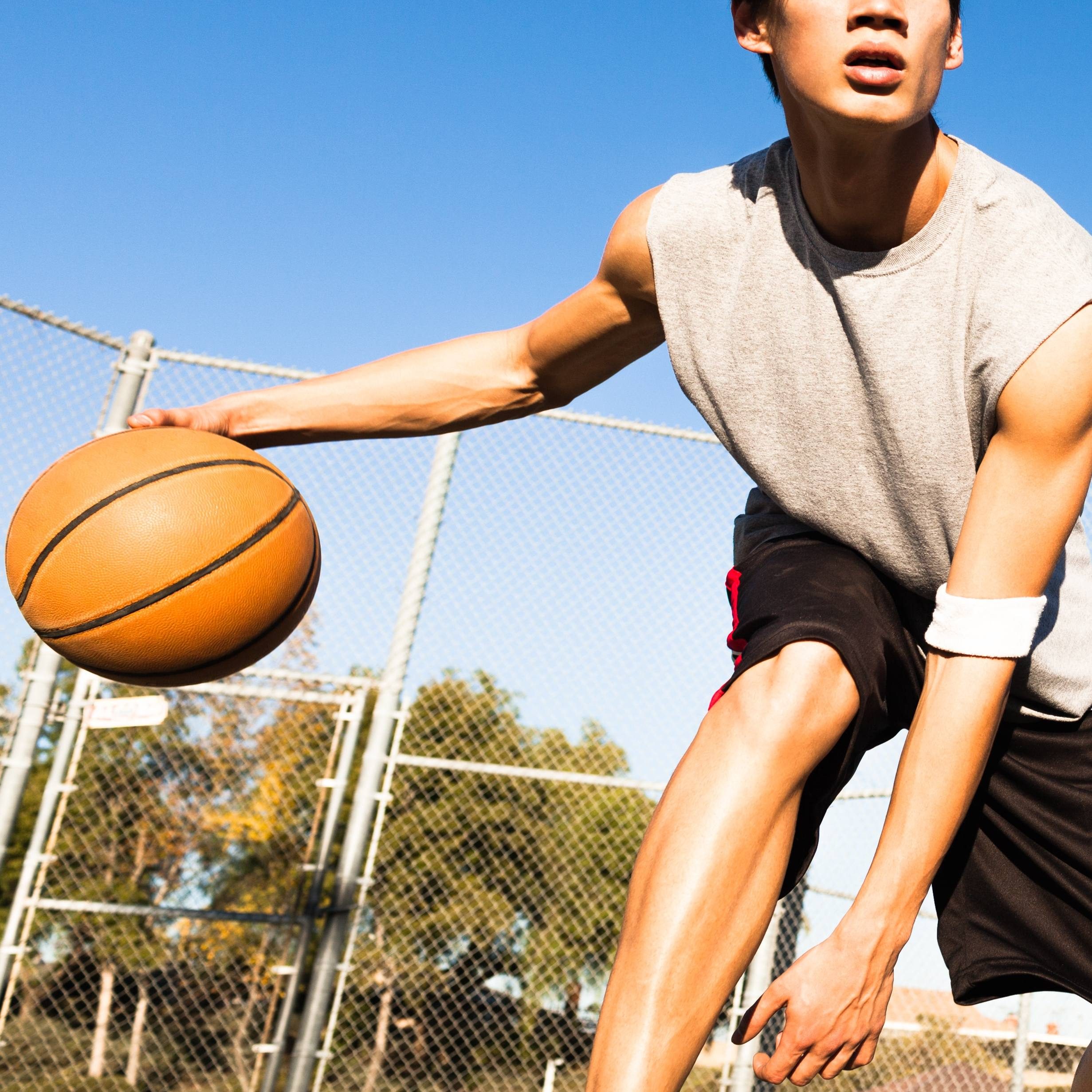 a young man playing basketball outside