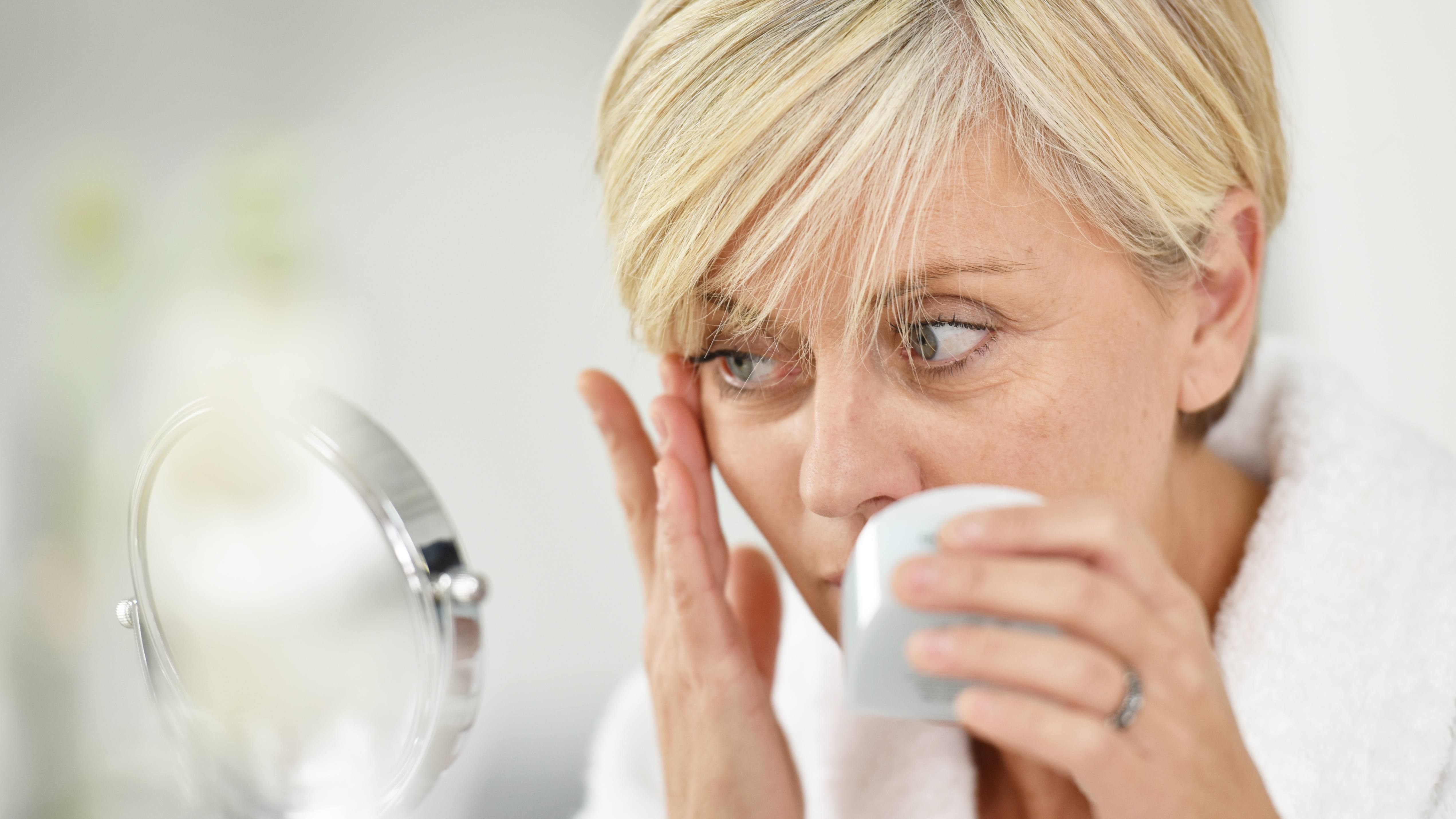 a middle-aged woman looking into a mirror at the wrinkles on her face