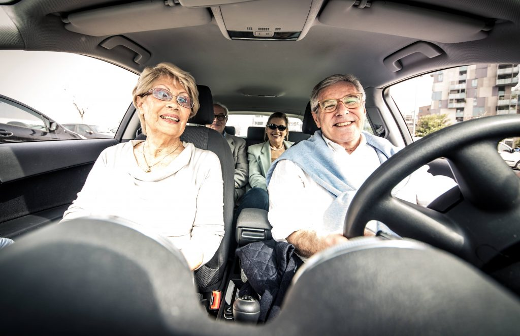 an elderly or senior man and woman driving in a car with a couple of friends in the back seat, laughing and smiling