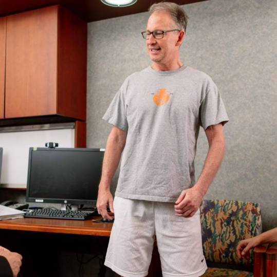 stem cell trial patient Chris Barr in shorts and a t-shirt, smiling and standing a clinic exam room