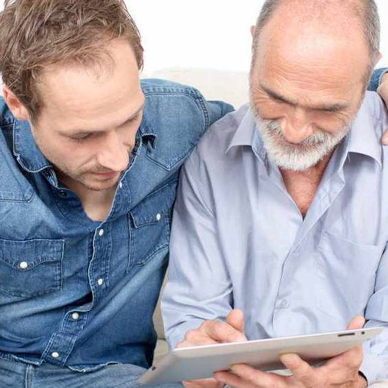 An older man reviews his living will advanced directive with his adult son.