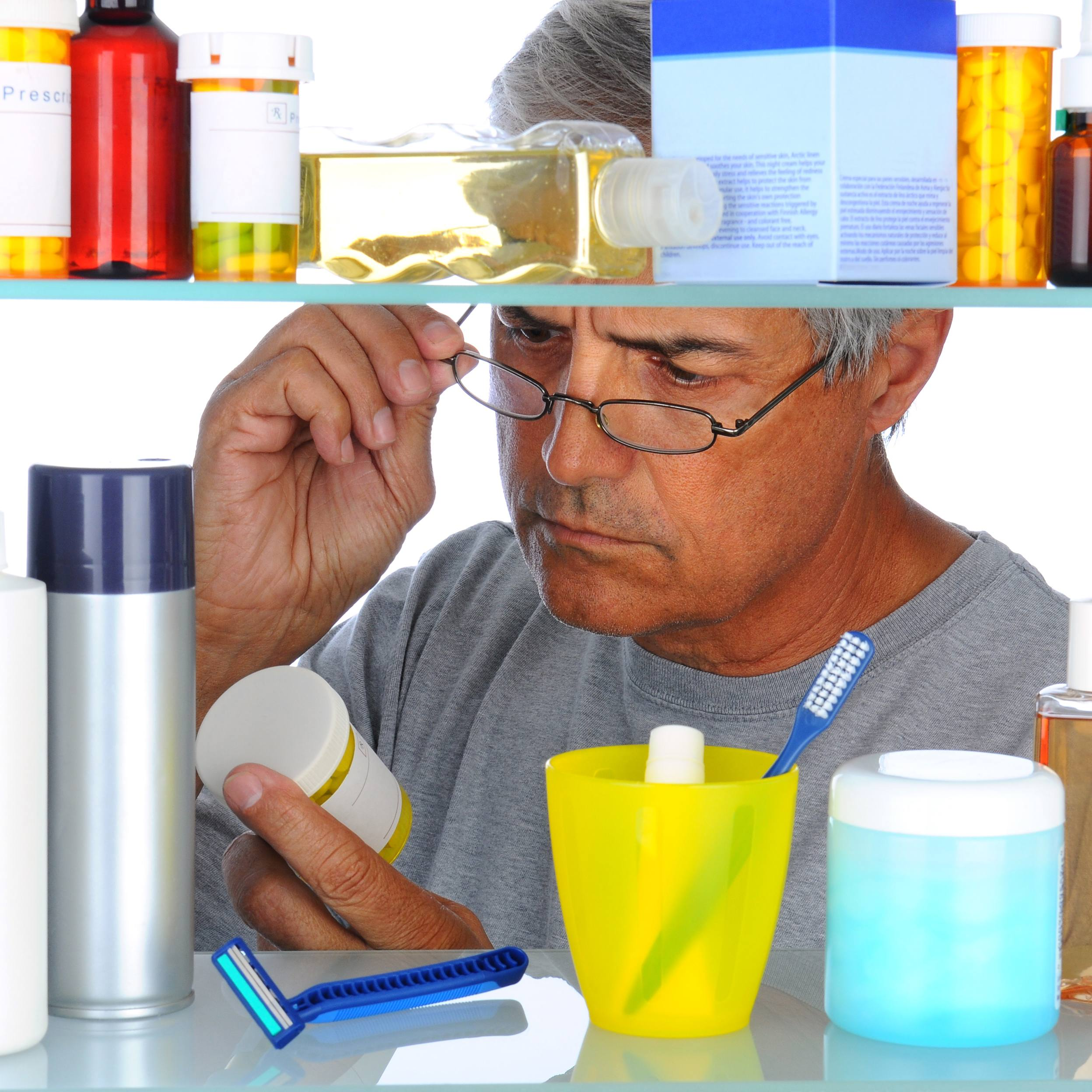 a middle-aged man reading a prescription bottle label in front of his open bathroom medicine cabinet