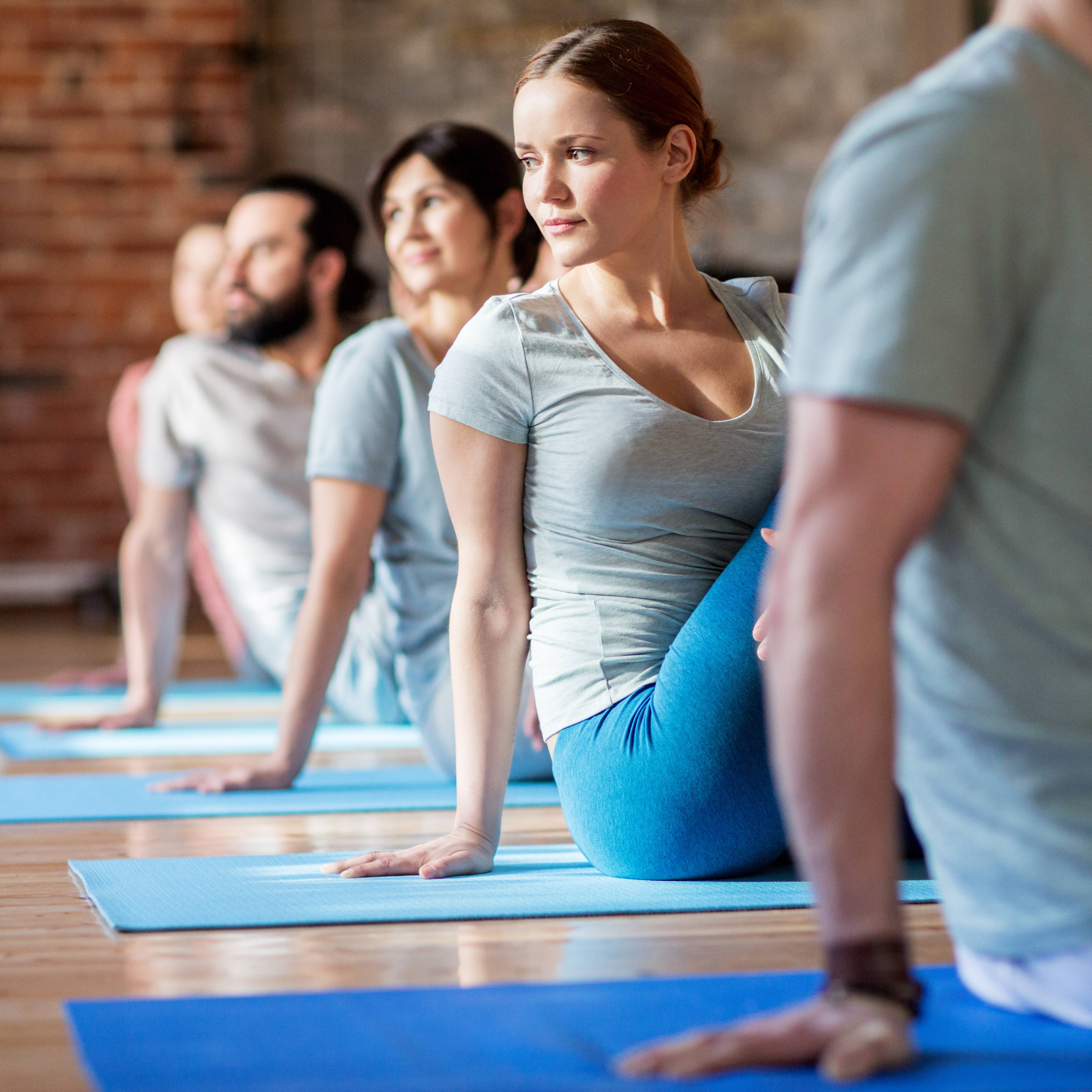 men and women in seated yoga pose