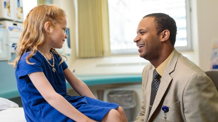 Waleed Gibreel, M.B.B.S., in a business suit smiling in exam room with a little Caucasian girl, pediatric patient, in a blue dress