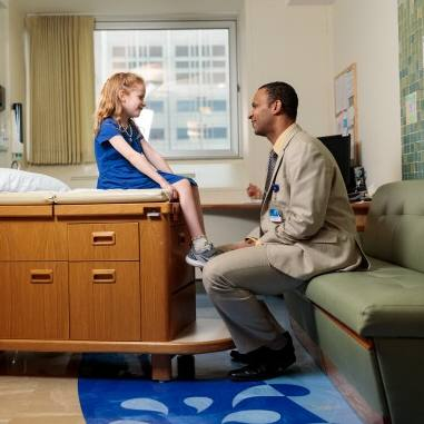 Waleed Gibreel, M.B.B.S., smiling in exam room with a little Caucasian girl, pediatric patient