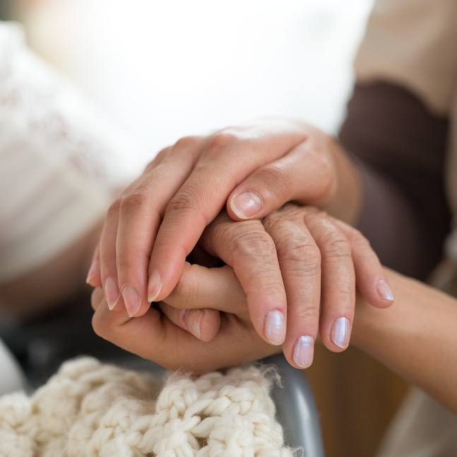 close up of a medical care giver holding a patient's hand, representing empathy and compassion