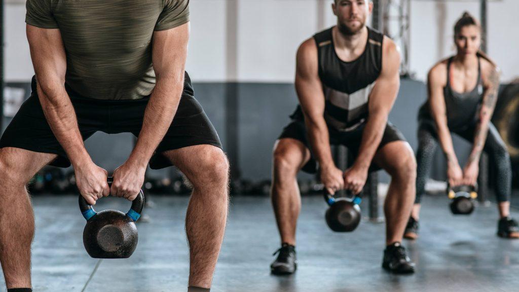 Un grupo de gente levanta pesas rusas en el gimnasio