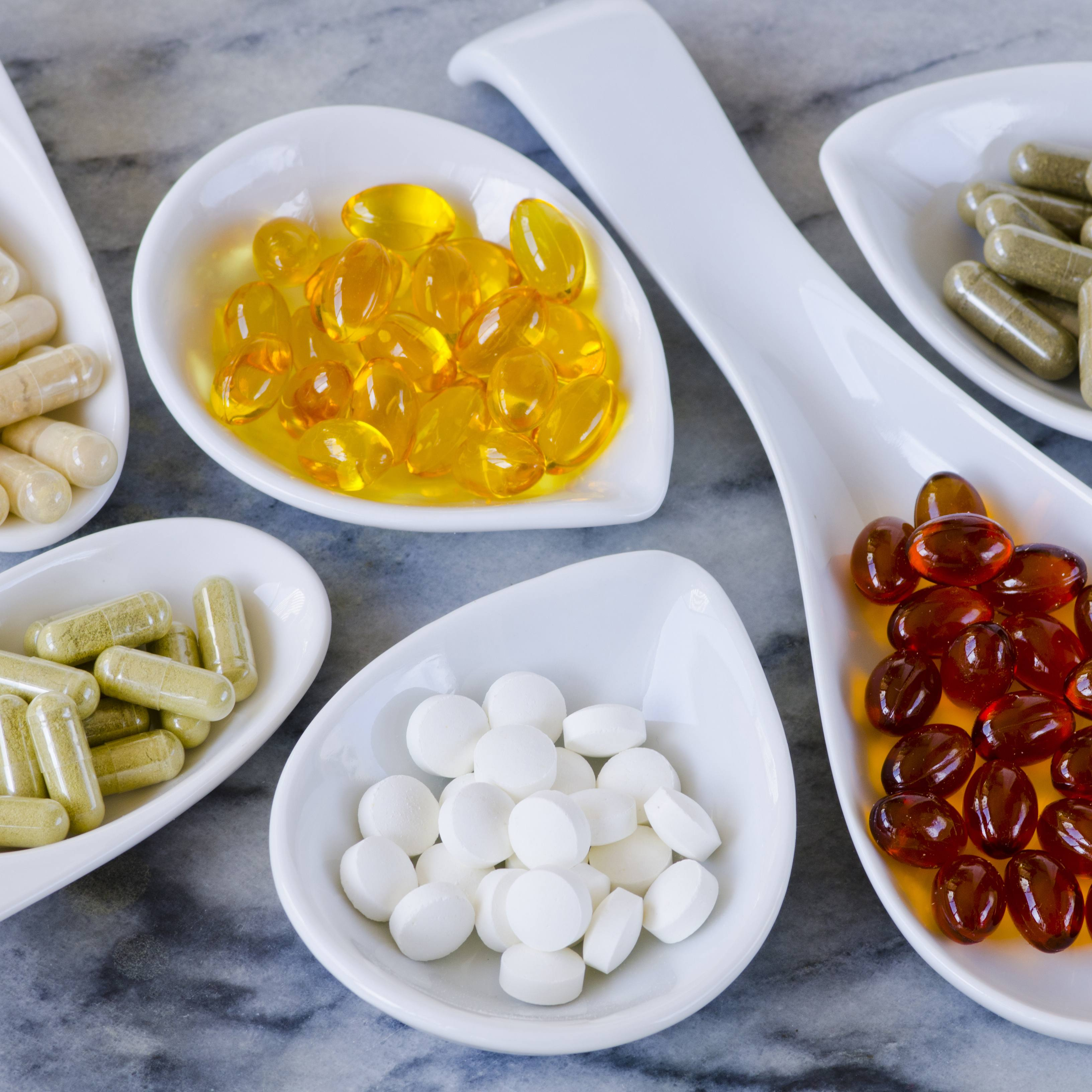 a variety of dietary supplements in white containers on a granite countertop