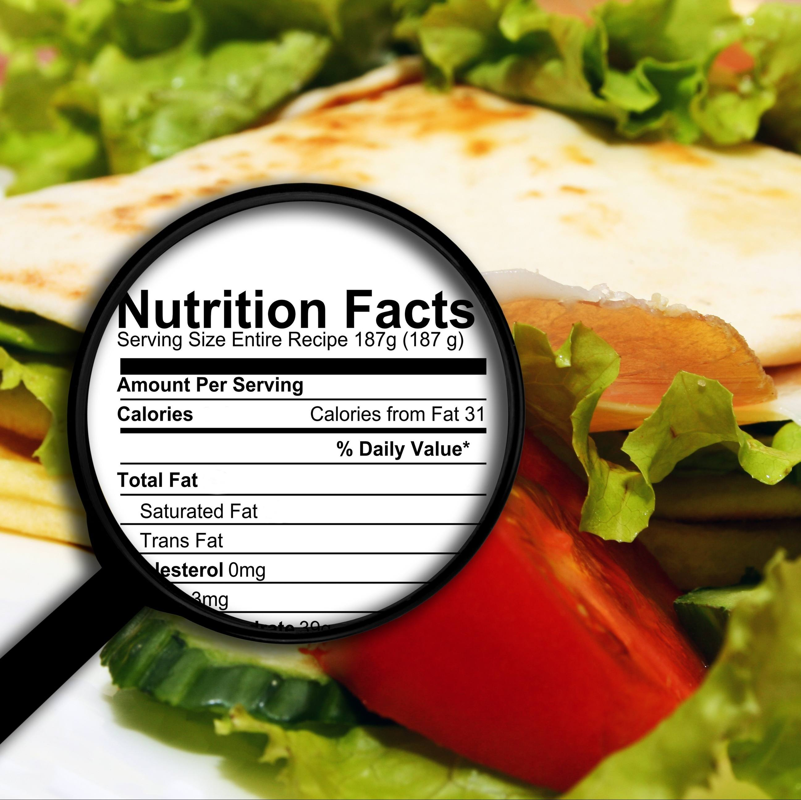close up of a healthy vegetable sandwich with lettuce and tomato and a nutrition facts label under a microscope
