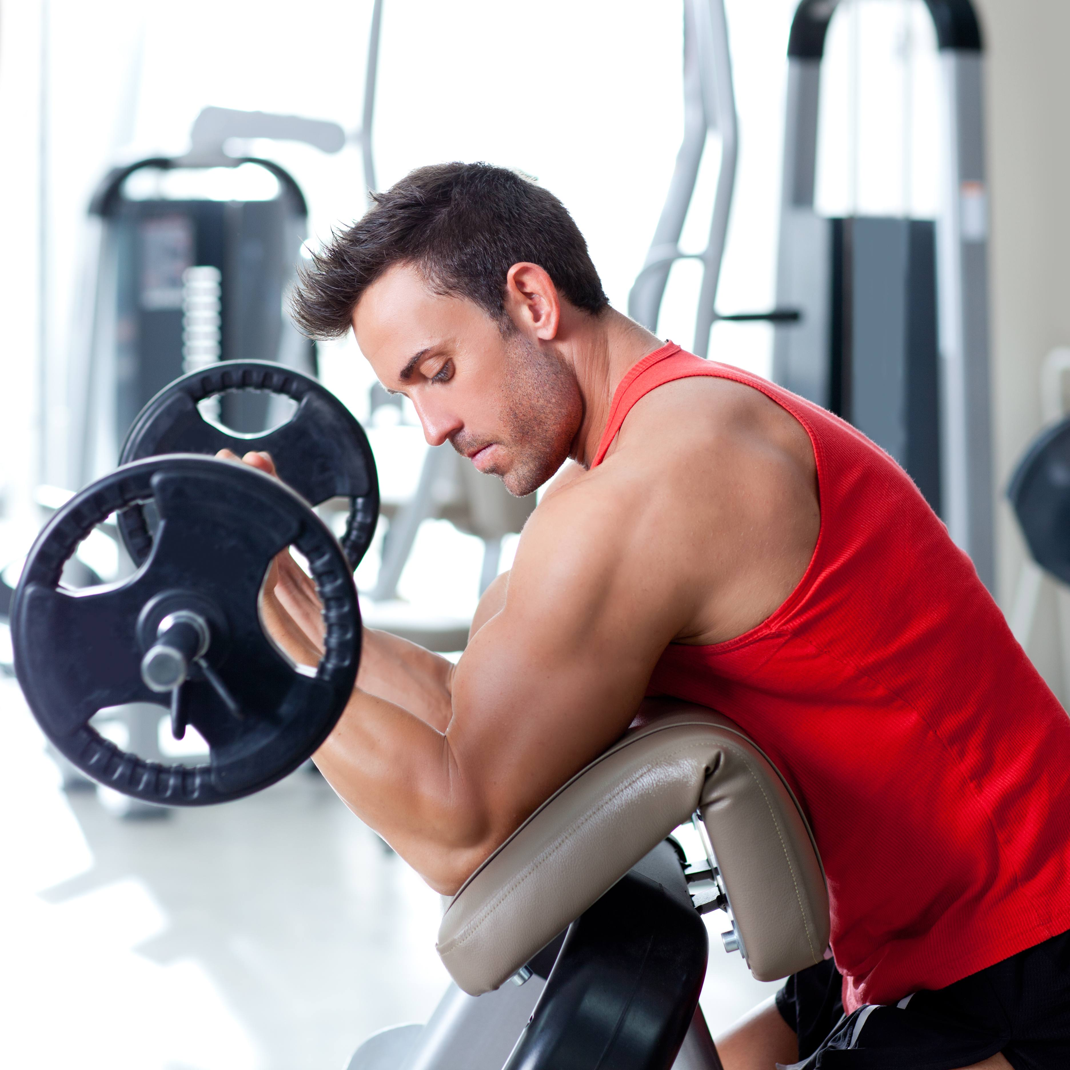 a young man using weight training equipment in a gym